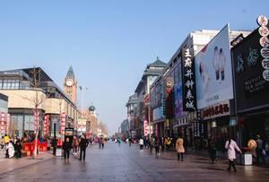 Breite Einkaufsstraße mit  Geschäften und Kirchturm in Beijing, China