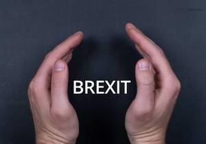 Brexit-Text mit Männerhänden auf schwarzem Untergrund