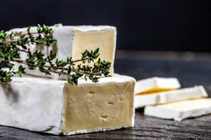 Brie cheese with fresh thyme on black background (Flip 2019)