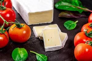 Brie-Käse mit Kräutern und Kirschtomaten auf einer schwarzen Schieferplatte