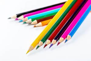 Bright colored pencils on white background. The concept of preparation for school