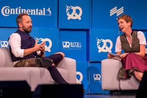 Britta Weddeling lächelt und Drew Houston erzählt seine Geschichte als Dropbox-Gründer auf der Bühne von Bits und Pretzels