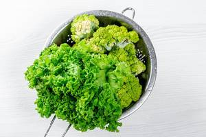 Broccoli and lettuce with water drops in a sieve. Top view