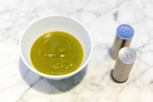 Broccoli Creme-Suppe in einer weißen Schüssel auf Marmortisch mit Salz und Pfefferstreuer