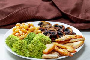 Broccoli with chickpeas, mushrooms and chicken on a white plate (Flip 2019)