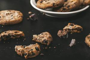 Broken cookies with pieces of chocolate on a black background (Flip 2019)
