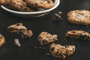Broken cookies with pieces of chocolate on a black background