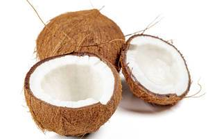 Broken fresh coconut halves and whole coconut on a white background (Flip 2020)