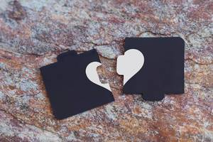 Broken heart made of two pieces of jigsaw puzzle on the marble. Broken heart, loneliness, divorce and unhappy relationships concepts.jpg