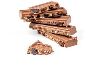 Broken pieces of milk chocolate with nuts and raisins (Flip 2020)