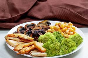 Brokkoli mit Kichererbsen, gebackenen Pilzen und Hühnchen, auf weißem Teller