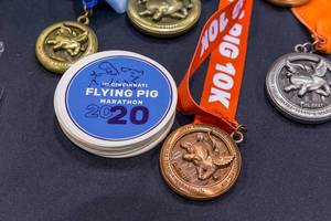 Bronze-, silver-, and gold medals next to patches of the Cincinnati Flying Pig Marathon 2020
