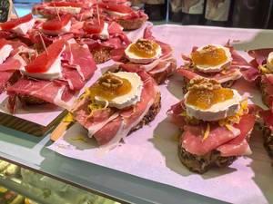 Brot-Häppchen mit Serano Schinken, Weichkäse, Gelee und einer Walnuss