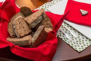 Brotscheiben in auf roter Serviette in Korb vor weihnachtlich gedecktem Tisch