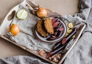 Brotzeit mit frischer Wurst, Zwiebeln und Knoblauch auf Holztablett