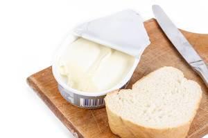 Brotzeit mit Streichkäse, einem Stück Weißbrot und Messer auf Holzbrett vor weißem Hintergrund