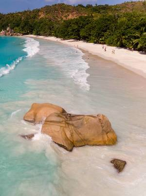 Brown granite rock covered by waves of the Indian Ocean with tourists on the white beach Anse Lazio in the background in Praslin, Seychelles