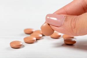 Brown pills on a white wooden background and one in a woman