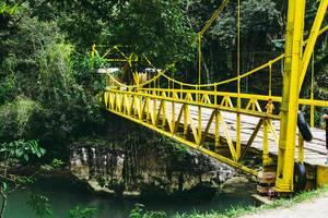 Brücke mit Holzlatten und gelb lackiertem Stahlgerüst führt über kleinen Fluss