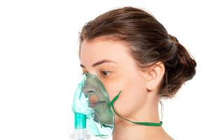 Brunette woman with nebulizer mask on his face
