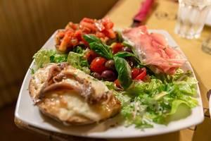 Bruschetta mit Sardinen, Proscciutto und Tomaten auf Salat mit Oliven und Basilikum in Mimi e Cocos Weinbar in Rom