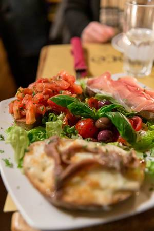 Bruschetta with sardines, proscciutto and tomato on salad with olives and basil at Mimi e Coco wine bar in rome