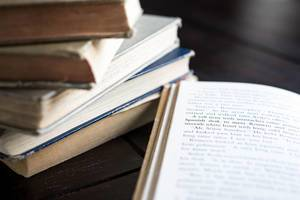 Bücherstapel und ein aufgeschlagenes Buch
