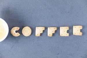 Buchstaben formen aus Biscuit neben einer Kaffeetasse