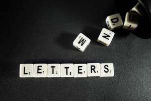 """Buchstaben-Würfel ergeben das Wort """"Letters"""", auf einer schwarzen Oberfläche"""