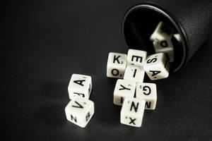 Buchstaben-Würfel fallen aus einem schwarzen Würfelbecher