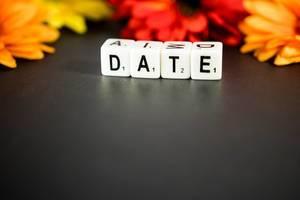 Buchstabenwürfel legen das Wort Date, umgeben von Sommerblumen
