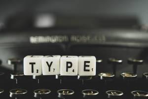 """Buchstabenwürfel legen das Wort """"Type"""" und liegt auf einer Retro-Knopftastatur"""