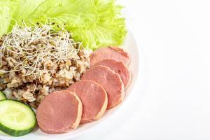 Buchweizenporridge mit Wurstscheiben, Salat und Gurke, neben Alfalfa-Mikrogrün