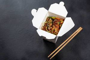 Buckwheat soba noodles with vegetables and fish in a cardboard box with chopsticks on a black background
