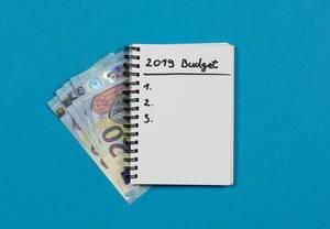 Budget Berechnung für das Jahr 2019 - Spiralheft mit Liste und Geld auf blauem Hintergrund