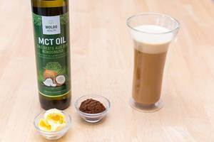 Bulletproof Coffee in a Glass with MCT Coconut Oil and Butter on a Wooden Table