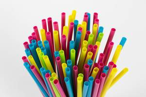 Bunch of Colorful Plastic Straws standing on white Background