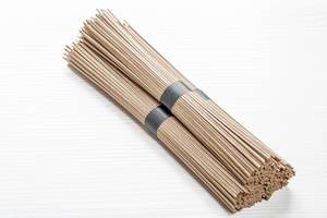 Bundles of raw buckwheat soba noodles on white wooden background