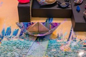 Bunt bemalte Papierschiffe in verschiedenen Größen auf künstlerischem Untergrund