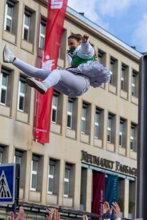 Bunt gekleidete Frau wird in die Luft geworfen - Kölner Karneval 2018