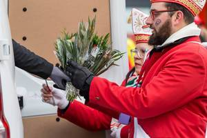 Bunt gekleideter Mann nimmt Blumen entgegen - Kölner Karneval 2018