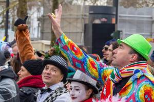 Bunt gekleideter Mann versucht eine Blume zu fangen - Kölner Karneval 2018