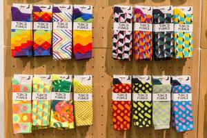 Bunt gemusterte Socken von Takapara führen zu garantierter Aufmerksamkeit an Holzwand