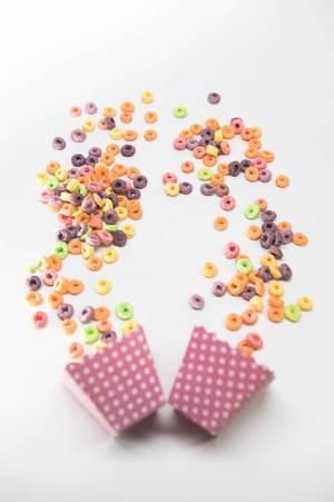 Bunte Cornflakes fallen aus pink-weißen Pappschachteln auf einen weißen Untergrund