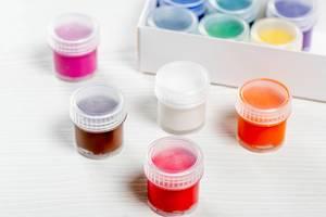 Bunte Farben in kleinen Schachteln auf braunem Holztisch
