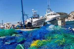 Bunte Fischernetze und Boote im Hintergrund