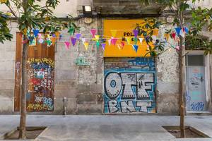 Bunte Girlanden zwischen Bäume gespannt, vor Graffiti an der spanischen Straße Carrer de la Riera Baixa in Barcelona