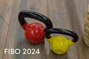 """Bunte Kettlebells in verschiedenen Gewichten, stehen auf einem Holzparkett, neben dem Bildtitel """"Fibo 2024"""""""