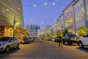 Bunte Lichterketten hängen kreuz und quer über der Straße und leuchten in allen Farben