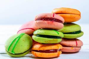 Bunte Macarons mit Füllung aufeinander gestapelt vor weißem Hintergrund